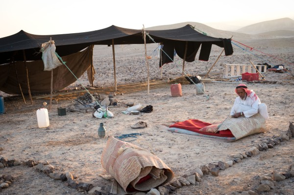 Abu putting away his bed at sunrise in the desert